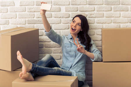 Attractive young woman is moving, making selfie using a smart phone and smiling while sitting among cardboard boxes Stock Photo
