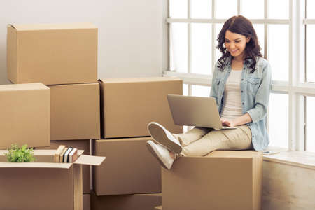 college dorm: Attractive young woman is moving, sitting among cardboard boxes, using a laptop and smiling