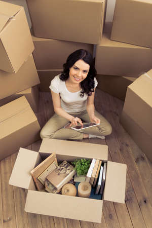 college dorm: High angle view of attractive young woman moving, using a tablet, looking at camera and smiling while sitting among cardboard boxes Stock Photo