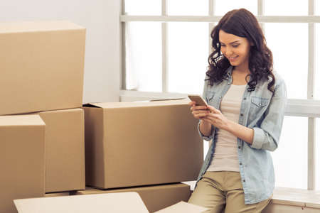 college dorm: Attractive young woman is moving, standing among cardboard boxes, using a smartphone and smiling