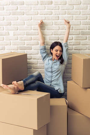 college dorm: Happy attractive young woman is moving, stretching hands and smiling while sitting among cardboard boxes