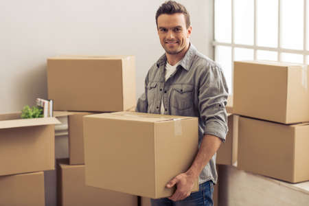 college dorm: Handsome young man is moving, holding a cardboard boxes, looking at camera and smiling