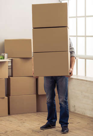 college dorm: Handsome young man is moving, holding a cardboard boxes that covering him Stock Photo