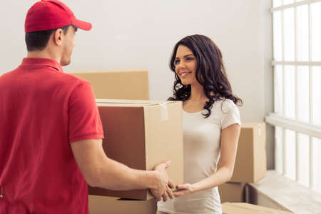 moving box: Attractive young woman is moving, giving a cardboard box to handsome delivery worker and smiling