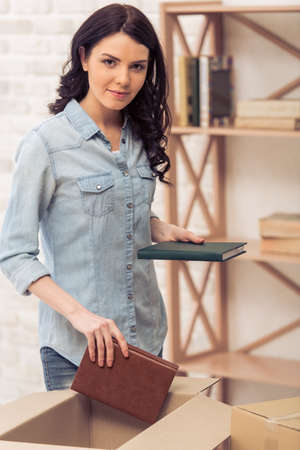 moving box: Attractive young woman is moving, looking at camera and smiling while packing book in cardboard box