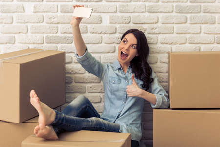 college dorm: Attractive young woman is moving, making selfie using a smart phone and smiling while sitting among cardboard boxes Stock Photo