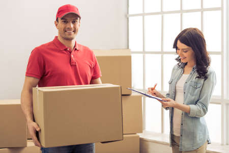 moving box: Attractive young woman is signing documents for moving. Handsome delivery worker is holding a cardboard box