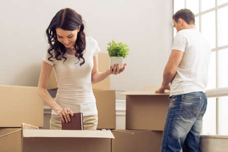 'young things': Attractive young couple is moving, smiling and looking through things while packing, standing among cardboard boxes
