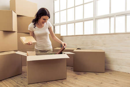 college dorm: Attractive young woman is moving, smiling and looking through things while packing, sitting among cardboard boxes