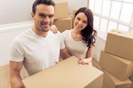 moving box: Attractive young couple is moving, looking at camera and smiling while standing among cardboard boxes. Man is holding a box