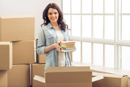 Attractive young woman is moving, packing books in cardboard box, looking at camera and smiling