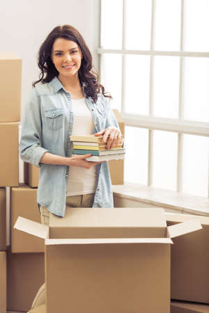 college dorm: Attractive young woman is moving, packing books in cardboard box, looking at camera and smiling