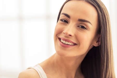 dark haired woman: Portrait of beautiful young dark haired woman looking at camera and smiling Stock Photo