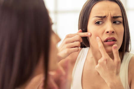 skin problem: Portrait of beautiful young woman squeezing pimples while looking at the mirror