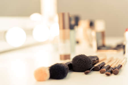 Close-up of makeup brushes lying on table in stylist room