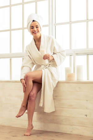 Beautiful girl in bathrobe is applying body lotion on her legs and smiling while sitting in bathroom