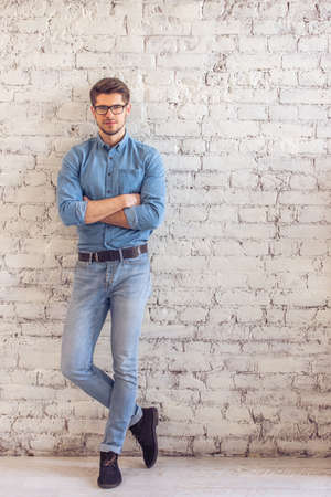full lenght: Full lenght portrait of handsome young man in jeans clothes and eyeglasses looking at camera and smiling, standing against white brick wall Stock Photo