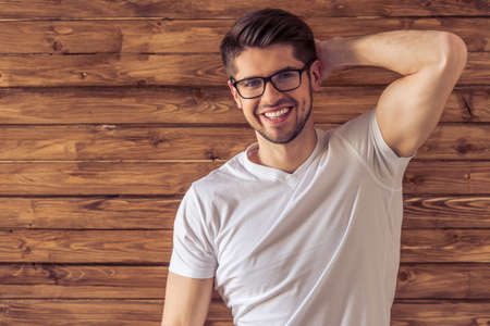 muscled: Portrait of handsome young man in eyeglasses looking at camera and smiling, standing against wooden wall