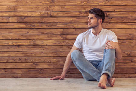 barefeet: Handsome pensive young man is looking away and thinking, sitting on floor against wooden wall