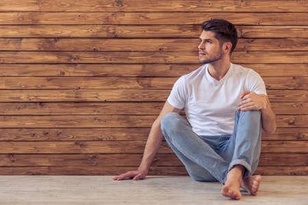 Knappe peinzende jonge man weg te kijken en na te denken, zittend op de vloer tegen de houten wand