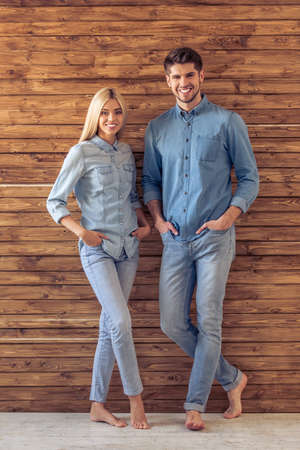 full lenght: Full lenght portrait of beautiful young couple in jeans clothes looking at camera and smiling, standing hands in pockets against wooden wall