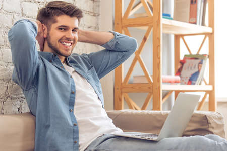 home keeping: Attractive young man is using a laptop, keeping hands behind head, looking at camera and smiling while sitting on sofa at home