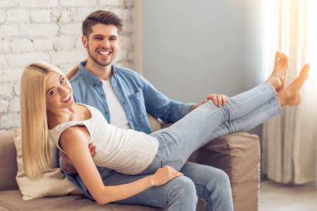 laps: Beautiful young couple is looking at camera and smiling while sitting on sofa at home. Girl is lying on her man laps