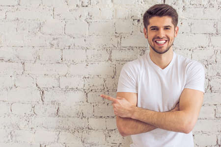 looking away from camera: Handsome young man is pointing away, looking at camera and smiling, standing against white brick wall