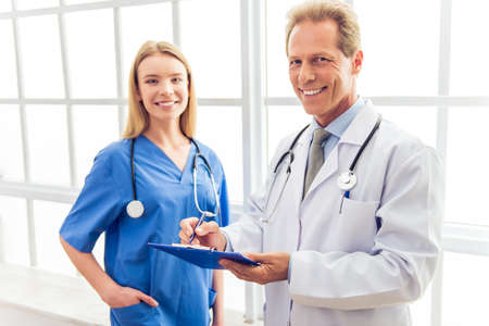 medical doctors: Beautiful young female doctor in blue and handsome middle aged doctor in white coat are making notes, looking at camera and smiling