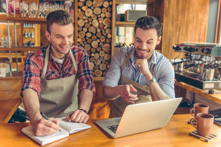 Two handsome young cafe workers are using a laptop, making notes, talking and smiling while standing at the bar counter
