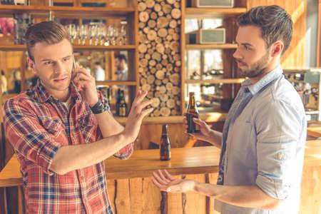 guardar silencio: Dos hombres j�venes est�n bebiendo cerveza en un caf� moderno urbano. Un hombre est� hablando por el tel�fono m�vil y se�alando a su amigo guardar silencio