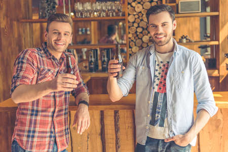 near beer: Two handsome young men are drinking beer, looking at camera and smiling, standing near bar counter in a modern urban cafe