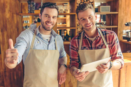 Two handsome cafe workers are using a tablet, looking at camera and smiling while standing at the bar counter. One guy is showing Ok sign