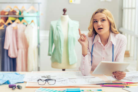 fashion clothing: Beautiful young designer is holding a tablet, pointing upward and thinking while working in dressmaking studio