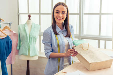 designer bag: Beautiful young designer is holding a shopping bag, looking at camera and smiling while working in dressmaking studio
