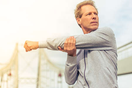 sports uniform: Handsome middle aged man in sports uniform is looking away and warming up during morning run Stock Photo
