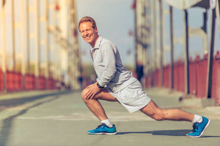 lunges: Side view of handsome middle aged man in sports uniform warming up, doing lunges, looking at camera and smiling during morning run Stock Photo