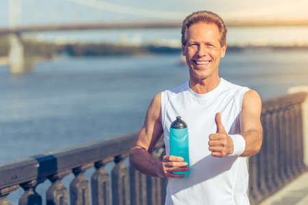 sports uniform: Handsome middle aged man in sports uniform is holding a bottle of water, showing Ok sign, looking at camera and smiling during morning run