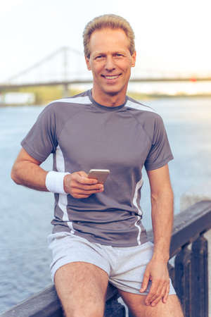 sports uniform: Handsome middle aged man in sports uniform is using smartphone, looking at camera and smiling, resting during morning run Stock Photo