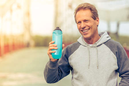sports uniform: Handsome middle aged man in sports uniform is holding a bottle of water  and smiling during morning run Stock Photo