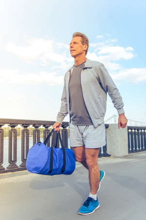 sports uniform: Handsome middle aged man in sports uniform is going with sport bag in his hand