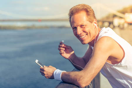 personas trotando: Handsome middle aged man in sports uniform and headphones is listening to music using smartphone, looking at camera and smiling