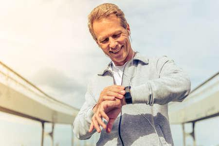 잘 생긴 중간 나이 든된 남자가 스포츠 유니폼 및 헤드폰 그의 시계를 찾고 아침 실행 동안 웃는