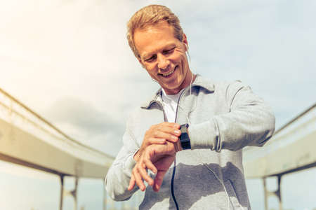 Handsome middle aged man in sports uniform and headphones is looking at his watch and smiling during morning run Stock Photo