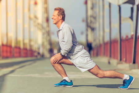 lunges: Side view of handsome middle aged man in sports uniform warming up, doing lunges and smiling during morning run