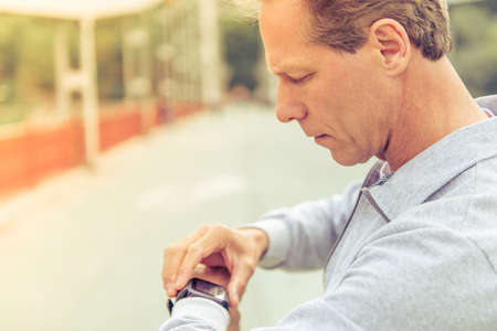 sports uniform: Side view of handsome middle aged man in sports uniform looking at his watch during morning run