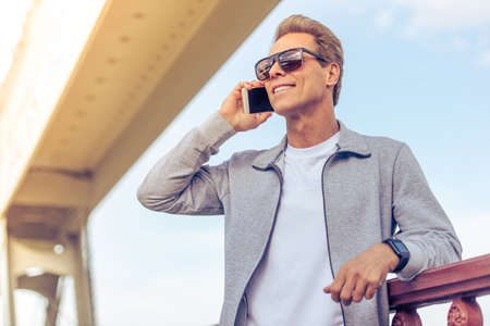 sports uniform: Handsome middle aged man in sports uniform and glasses is talking on the mobile phone and smiling while having break during morning run Stock Photo