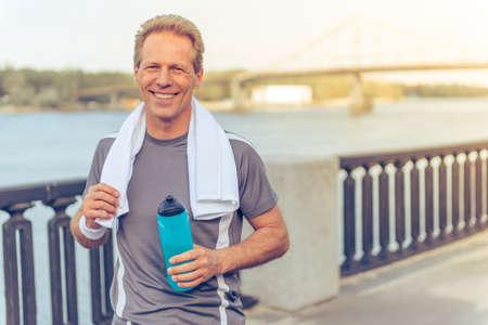 Gut aussehend Mann mittleren Alters in Sport Uniform ist eine Flasche Wasser, in die Kamera und lächelnd, während der morgendlichen Lauf ruht