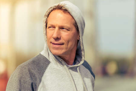sports uniform: Portrait of handsome middle aged man in sports uniform looking away and smiling during morning run Stock Photo