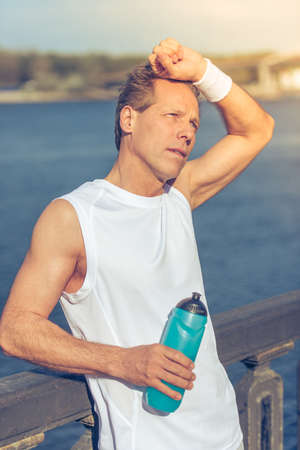 sports uniform: Handsome tired middle aged man in sports uniform holding a bottle of water and resting during morning run